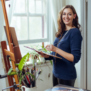 Artist Sarah Marie Lacy standing at her easel holding a palette and paintbrush
